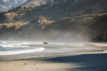 A surfer walking out of the water after an early morning surf session in Big Sur, CA