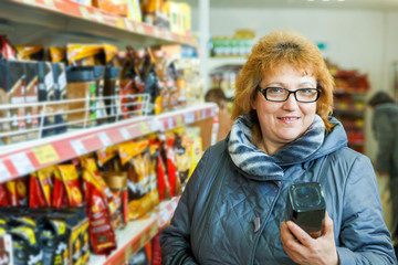Mature beautiful woman in a supermarket chooses coffee.