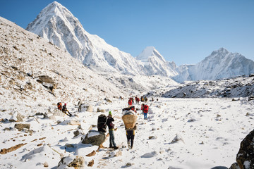 Hikers and porters walking on snowy landscape in Nepal