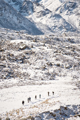 A line of trekkers walking along the Khumbu Glacier in the Himalayas