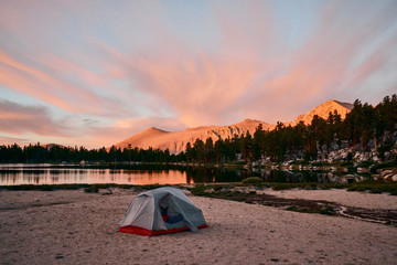 A tent at sunrise next to a high alpine lake in the backcountry of the Sierras