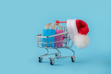 Online shopping, Christmas discounts packaging cardboard boxes, packages, Santa hat, in a cart on a blue background