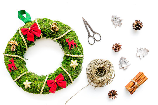 Process of making christmas wreath concept. Green christmas wreath near matherials and instruments, sciccors on white background top view