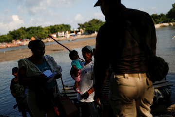 A Mexican migration officer checks the ID of people entering into Mexico from Guatemala across the Suchiate river, to prevent migrants from Central America to illegally cross it using rafts, in Ciudad Hidalgo