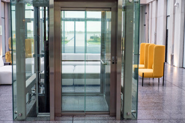 Lift with transparent glass doors in modern building