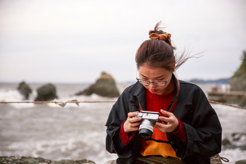 Young woman checks photos on back of camera at Wedded Rocks in Ise, Japan