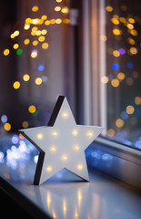 Glowing white LED star near window on warm bokeh background indoor.