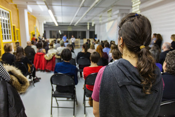 Crowd of 200 people listening to a conference in an industrial environment - alternative angle - Blurred audience mainly composed of young adults