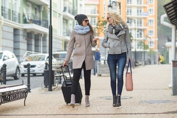 Two young smiling women with suitcase walking along city street. Urban background, autumn day, view from the back