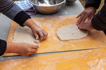 People are preparing pizza dough as part of an outdoor bread making workshop - Pictures taken during a bread and pizza making workshop with many people from all ages and generations.