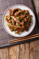 Traditional Asian beef teriyaki with green onions and sesame close-up on a plate. Vertical top view