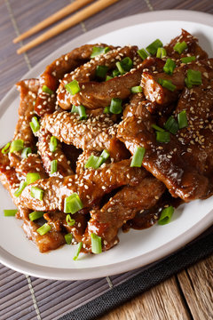 beef teriyaki with green onion and sesame close-up on a plate. vertical
