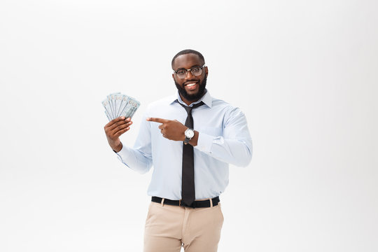 young cheerful black businessman holding and pointing at money isolated on white