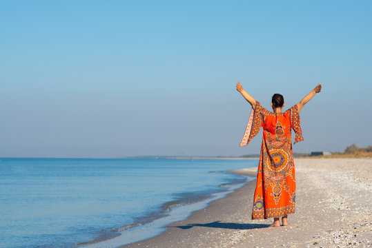 Woman in ethnic dress with open arms relaxes and meditates on a deserted beach