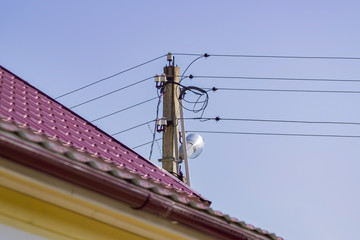 Electric pole and red tile roof on blue sky background. Power supply in countryside.