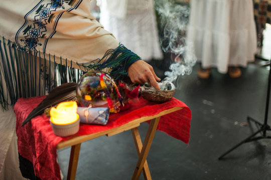 Woman in ceremonial robe is touching smoking sage from a mother of pearl abalone seashell, placed on a table with other sacred objects like feathers, candle and sacred stones