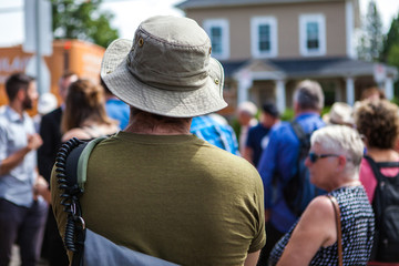 Man with a hat is listening to a public speech given in front of 100 people - Shot from the back during an alternative political gathering