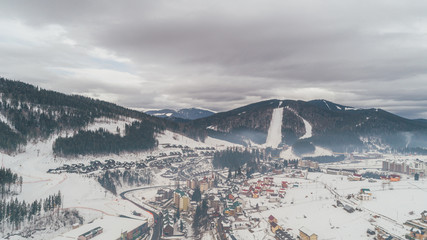 Aerial view of the mountains. Carpathians. Bukovel. Village. Winter. Snow. Forest. Trees