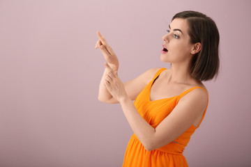 Portrait of beautiful young woman pointing at something on color background