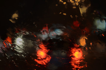 Background, colored light spots visible through wet glass in the dark when it rains.
