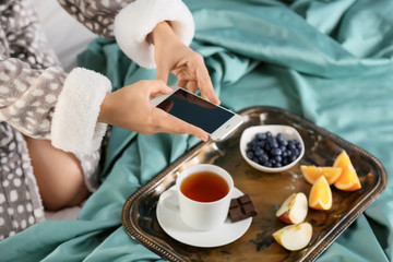 Young woman taking photo of breakfast with mobile phone on bed
