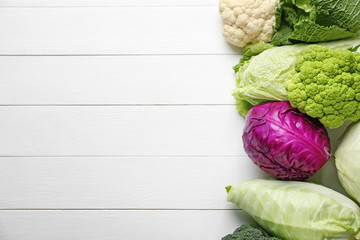 Different kinds of cabbage on white wooden background