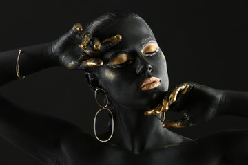 Beautiful woman with black and golden paint on her body against dark background Fototapete