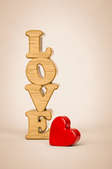 The word love and a red heart made of wood