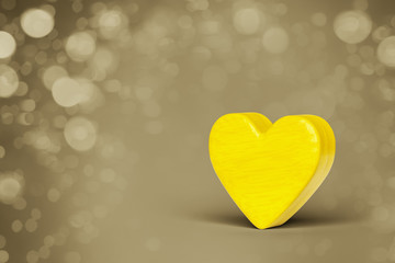 A yellow wooden heart in a bokeh lights background