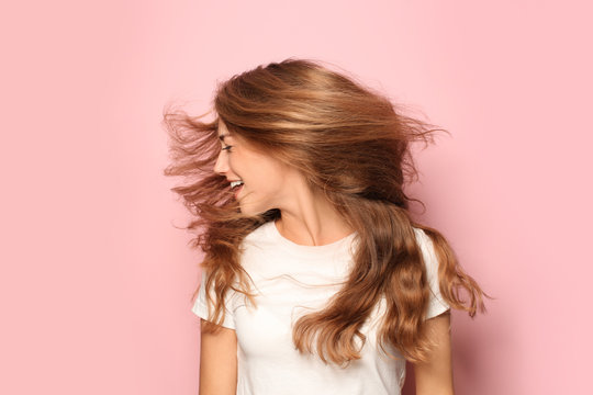 Portrait of beautiful young woman on color background
