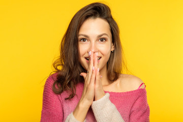 emotion face. overwhelmed perplexed shocked surprised astounded woman. young beautiful brown haired girl portrait on yellow background.