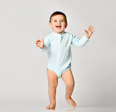 Infant child baby boy kid toddler in light blue body cloth make first steps on grey