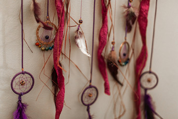 Very small dream catchers on leather threads and displayed with feathers and raffia ribbons - Closeup picture with narrow depth of field
