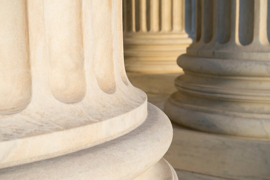 Lower detail of classical fluted columns in a colonnade in white marble lit by soft golden sunlight