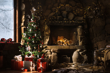 Christmas decorated fireplace and gifts in cozy chalet. Fire in stone fireplace