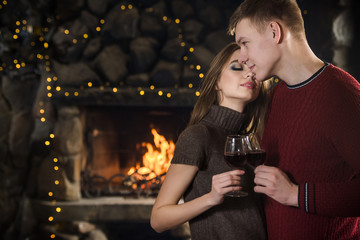 Happy couple with glasses near fireplace