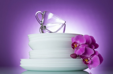 Clean plates and cups on bright purple background decorated with branch of orchid