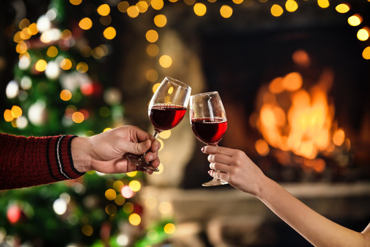 Celebrate christmas with red wine in glasses. Couple clink glasses near fireplace. Hands closeup