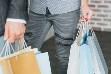 shopaholics and spending lifestyle. cropped shot of man and woman with multiple bags in hands.