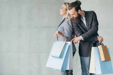 curiosity and buying addiction. man interested in womans shopping bags and stuff she purchased.