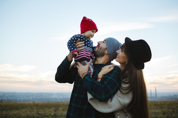 The dad holds his face in his arms with his mother. Photo session with family at sunset.