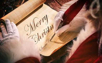 Santa Claus signing a handwritten Christmas scroll