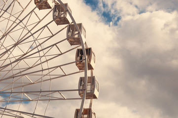 White ferris wheel in an amusement park, bottom view. Look upwards. Sky background with clouds with place for text.