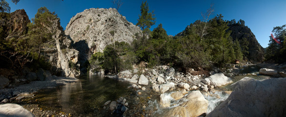 Panorama of the canyon and the mountain river against the blue sky