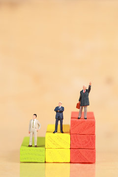 Miniature people: businessman standing with wooden podium using as background (Financial and Business competition concept)