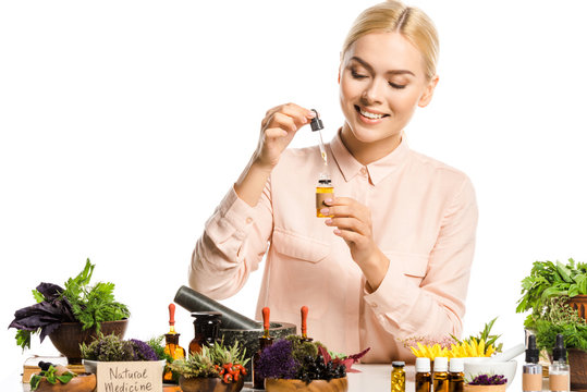 smiling woman making essential oil isolated on white