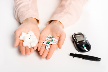 cropped image of woman holding glucometer strips and refined sugar isolated on white, diabetes concept