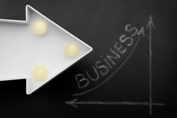 Business and finance inscription. Simple diagram showing succes handdrawn on a black chalkboard. Decorative arrow.