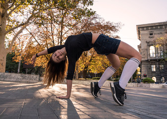 Outdoor autumn lifestyle image of a young pretty chestnut haired caucasian girl having fun and dancing on the street. Cute casual outfit in front of building.