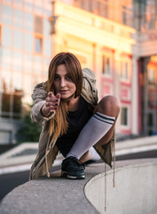Outdoor lifestyle image of a young pretty chestnut haired caucasian girl pointing, sitting, having fun and dancing on the street. Cute casual outfit in front of glass building.